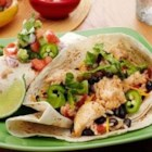 Speedy Chicken and Black Bean Burritos - Chunks of spicy chicken are roasted with rice, black beans, and zesty tomatoes for a quick and hearty Mexican-inspired dinner.