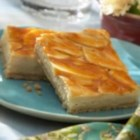 Apple Caramel Cheesecakes Bars - Easy caramel cheesecake bars are topped with apple slices and a final layer of Marzetti(R) Old Fashioned Caramel Dip after the bake.