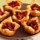 Smoked Sausage Cups - These bite-sized appetizers feature spicy kielbasa flavored with Dijon-style mustard and marmalade atop flaky puff pastry cups.