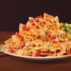 Classic Nachos with a Kick - Fiery shredded cheese adds the zing to these nachos that are topped with fresh chopped tomatoes and cilantro.