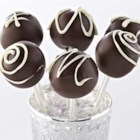 Triple Chocolate Cake Pops - Rich dark chocolate cake and chocolate buttercream frosting are formed into little cake balls, then dipped in melted dark chocolate and drizzled with white chocolate.