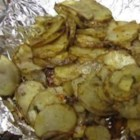 Hot Off the Grill Potatoes - Potato slices seasoned with fresh herbs and Parmesan cheese are wrapped in foil and cooked over a grill until tender.