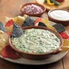 Festive Spinach Queso Dip - This crowd-pleasing cheesy, peppery dip with spinach and pimento peppers gets a creamy lift with the addition of sour cream.