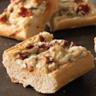 Cheesy Italian Pizza Loaf - Baguette halves are spread with a creamy blend of cheese, sun-dried tomatoes, and green onions, then topped with grated cheese and baked until toasty.