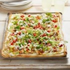 Chicken Club Pizza - Chicken, bacon, and cheese are baked on a ranch dressing and mayo sauce and, when the crust is golden brown and ready to serve, the pizza is topped with lettuce and chopped tomatoes.