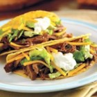 Slow-Cooked Taco Shredded Beef - Ground beef is good in tacos, but this fork-tender shredded beef makes good tacos even better. This slow cooker dish is perfect for buffets, tail-gating or casual family dinners.