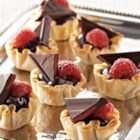 Raspberry Chocolate Tassies - Pretty little phyllo shells are filled with rich, dark chocolate and topped with a triangle of raspberry-filled chocolate. Garnish with a fresh raspberry, if you like!