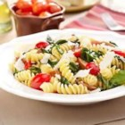 Fusilli with Grape Tomatoes and Sausage - Chunks of hot Italian sausage and corkscrew pasta are cooked with mixed greens and grape tomatoes in this quick and colorful dish.