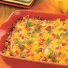 Enchilada Bean Dip with Corn - Browned ground beef, zesty tomatoes, refried beans, and chili powder are baked with cheese for this crowd-pleasing hot dip.