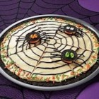 OREO Spider Web Cookie Pizza - Calling ghouls and goblins of all ages! This 'spooktacular' dessert features an OREO Cookie crust topped with a creamy combination of chocolate pudding and whipped topping. A chocolate spider web and a few cookie spiders add the perfect finishing touch.