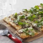 Caramelized Onion and Arugula Pizza - Create your own gourmet pizza topped with caramelized onions, fresh rosemary, arugula, and pine nuts on a cheesy, homemade crust.