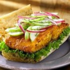 Grilled Salmon Sandwich with Green Apple Slaw - For a fresh alternative to predictable burgers and sausages, try this gourmet sandwich at your next barbecue. The savory-glazed salmon and crunchy, sweet-tart apple topping are an inspired combination.