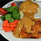 Sunday Sticky Chicken - Seasoned fried chicken is slow-cooked in milk and chicken broth, and served sticky with a thick gravy.