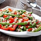 Greek Green Bean Salad - A new twist on a summertime favorite: green beans, cherry tomatoes are tossed with fresh parsley feta cheese and a greek dressing to make a healthy green bean salad.