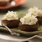Cheesy Mashed Potato Stuffed Mushrooms - These Cheesy Mashed Potato Stuffed Mushrooms are so elegant your guests will think you slaved over them. Your secret is safe with us.