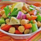 Garbanzo Bean and Pepper Salad - I made up this recipe for a cool summer dish to take to a picnic. I just threw together things I had on hand and it became a hit! You may substitute your favorite type of bean for the garbanzos. Any firm bean will do. You may omit the jalapeno altogether. This salad will work as a main course and is very satisfying and colorful. The different tastes and textures are very pleasing. Serve cold.