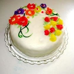 Rolled buttercream fondant with gumdrop flowers on orange cake