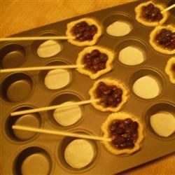 Filled pies in mini muffin pan, waiting for top crusts