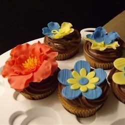Gum paste flowers on caramel cupcakes with creamy chocolate frosting on top.