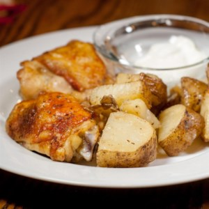 Garlic Roasted Chicken and Potatoes Recipe - Chicken and potatoes bake in butter with 24 cloves of garlic and a little maple syrup at the end for sweetness. Don't worry, the garlic cooks down to a mellow, soft texture that's perfect to spread over the buttery chicken.