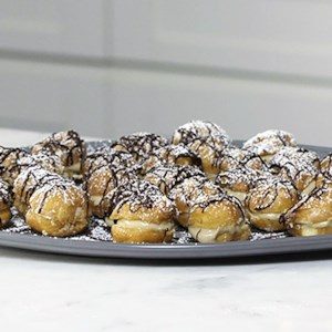 Baileys Irish-Coffee Doughnut Profiteroles Recipe and Video - Ordinary doughnut holes become fancy profiteroles when piped full of a custard cream containing both Baileys Irish Cream and Irish whiskey!