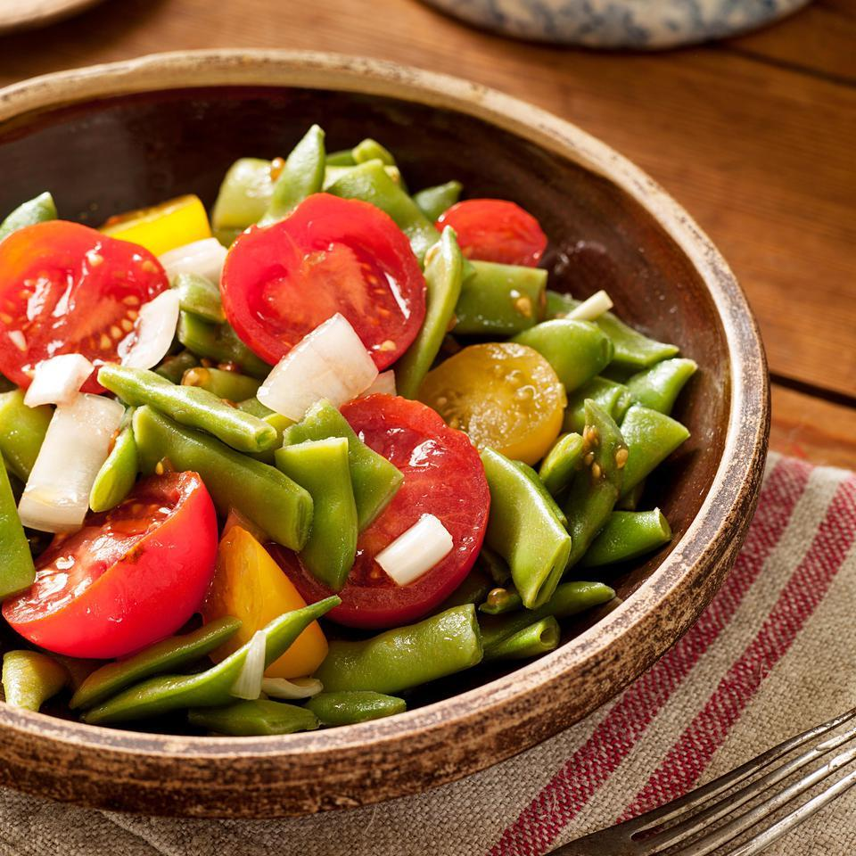 "At first glance, you may think that vinegar or lemon juice has been inadvertently omitted from the ingredient list of this green bean and tomato salad recipe. Not so. The juice of tiny ripe cherry tomatoes, called ""tommy toes"" in parts of the mountain South, is acidic enough that you don't need vinegar or lemon juice, and also contributes subtle sweetness—the perfect counterpoint to fresh beans."