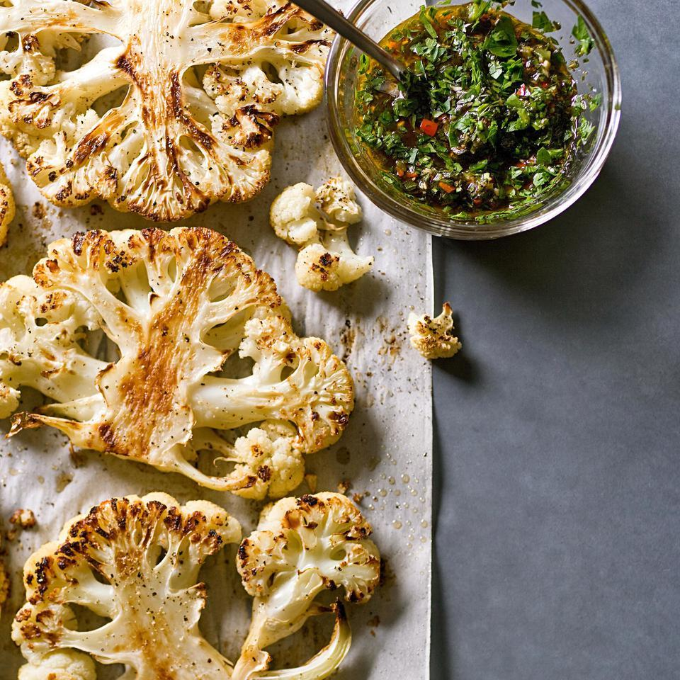 In this stunning, healthy cauliflower recipe, a head of cauliflower is cut into thick slabs then roasted until caramelized and served with chimichurri, a garlic-herb sauce. Each head of cauliflower will provide 2 to 3 steaks from the center—the sides tend to crumble. For a truly show-stopping presentation, use the center portion of 2 heads and save the rest of the cauliflower for another recipe that calls for cauliflower florets.