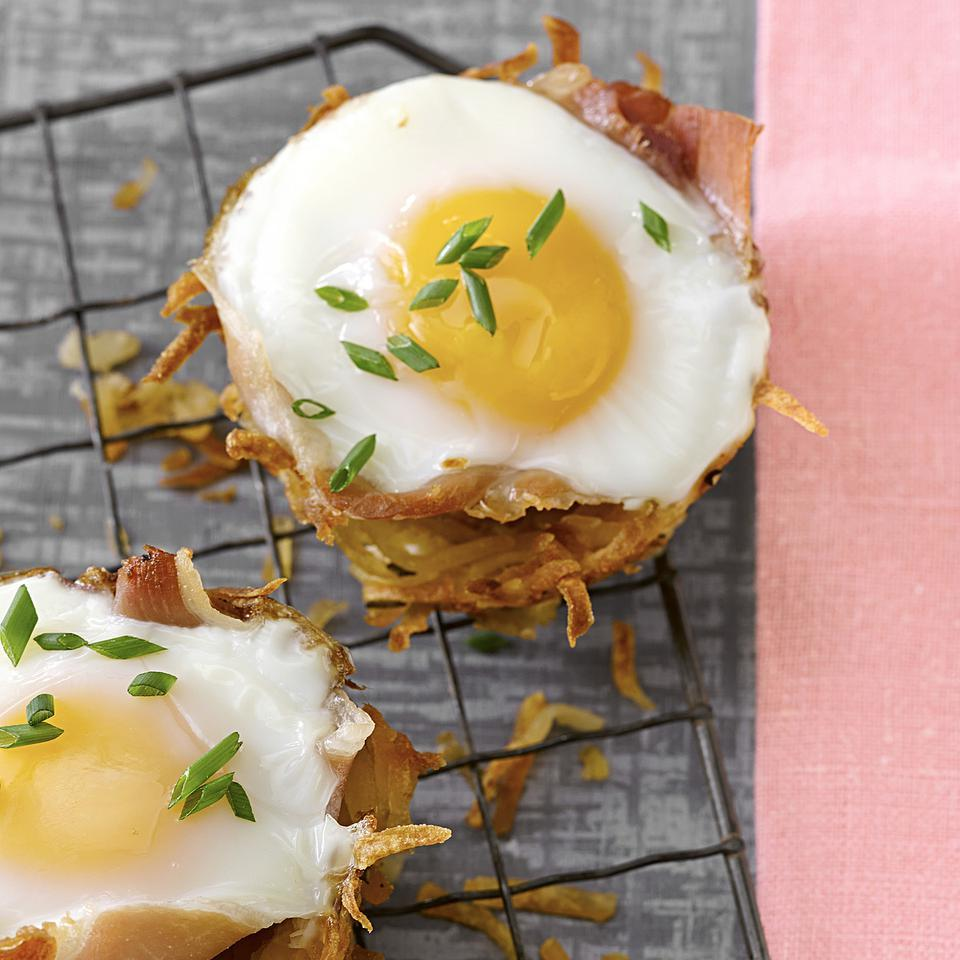 "Wow your brunch guests with this adorable muffin-tin recipe of baked eggs in a ""nest"" of prosciutto and hash browns. Make sure you really wring out as much liquid as you can from the potatoes before you bake them—it will prevent the cups from sticking in the muffin tin."