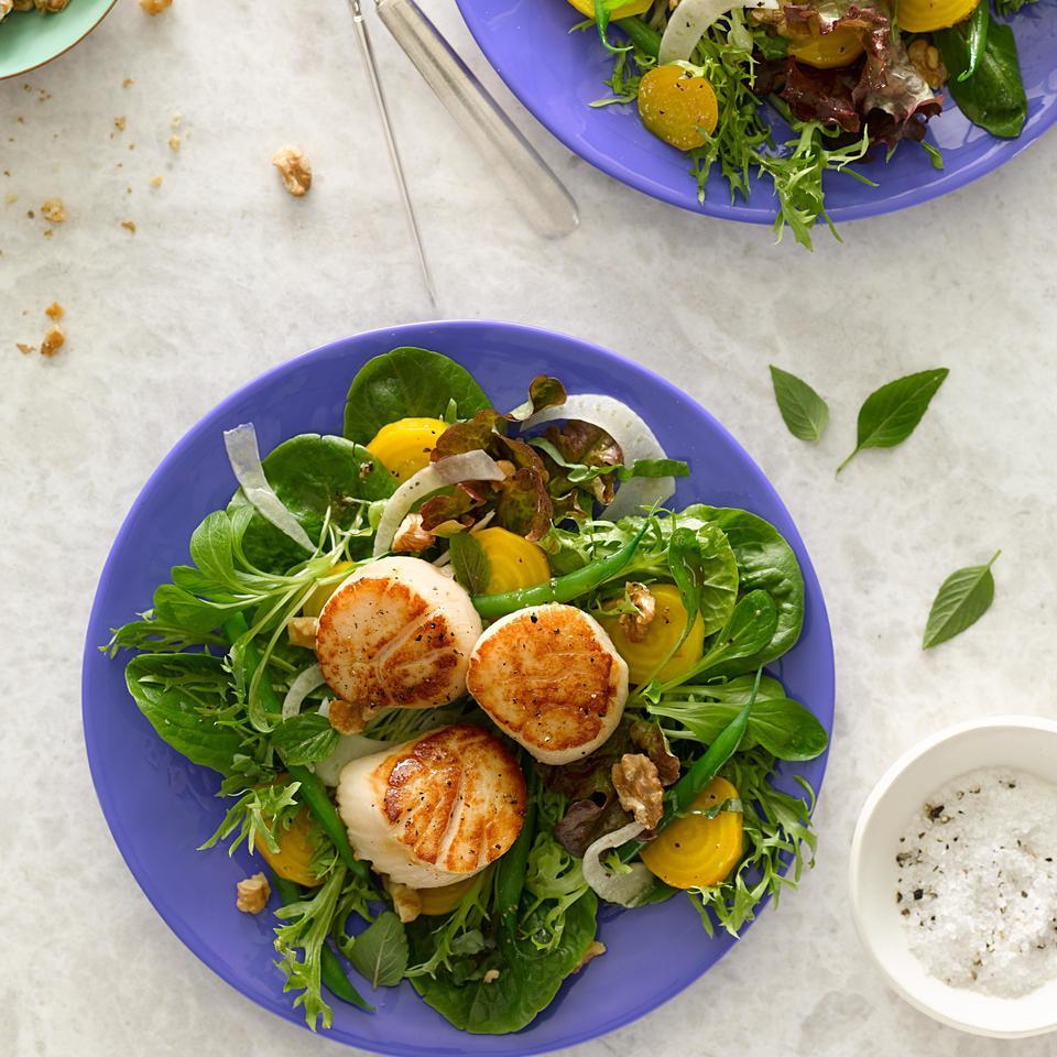 Lemony seared scallops and a walnut vinaigrette top this healthy dinner salad. When shopping for scallops, avoid those treated with sodium tripolyphosphate (STP); it can make them mushy and the scallops won't brown properly. Some scallops have a small white muscle on the side; remove it before cooking.