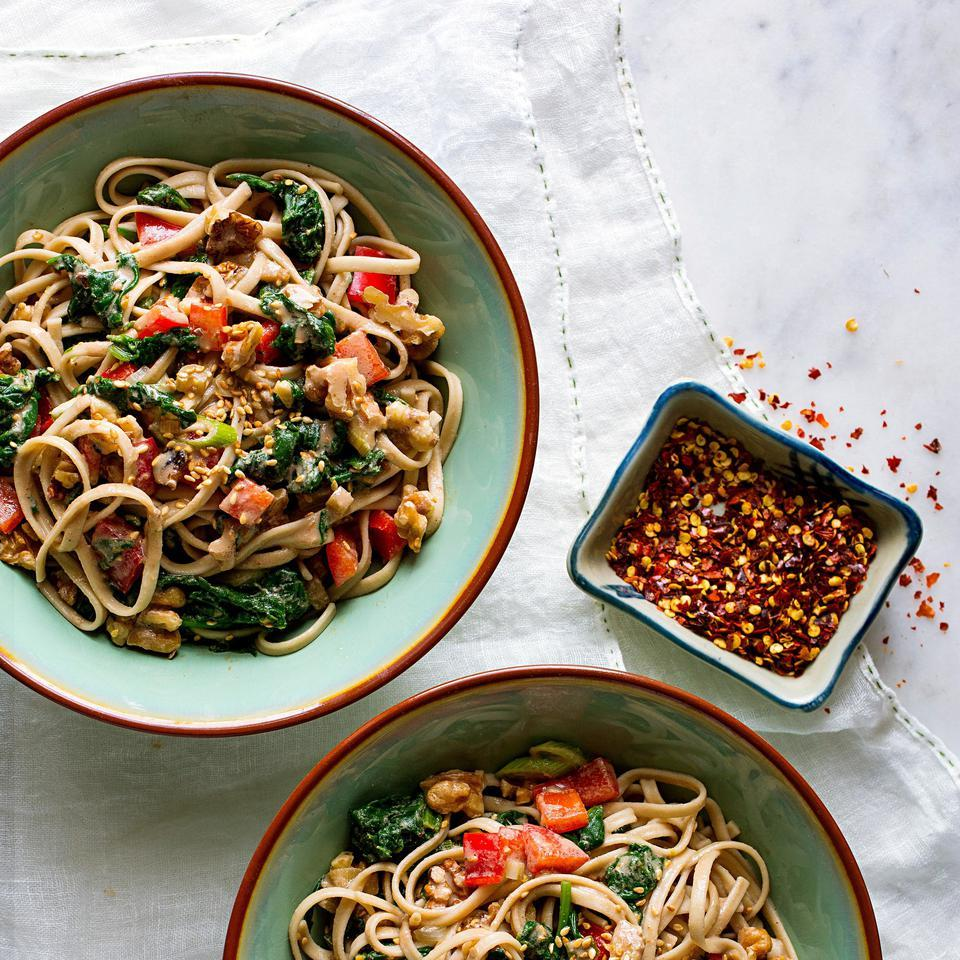 In this riff on Asian dan dan noodles, spinach and red bell peppers are tossed with a sesame-chile-soy sauce and topped with walnuts. If you want to bump up the protein, add tofu, seitan or even chopped egg.