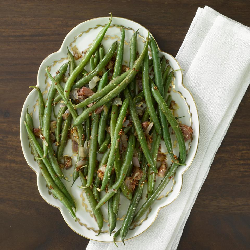 In this easy vegetable side recipe, green beans are tossed with crispy bits of pancetta, shallot and whole-grain mustard after cooking. If you can't find pancetta, bacon is a perfect alternative.