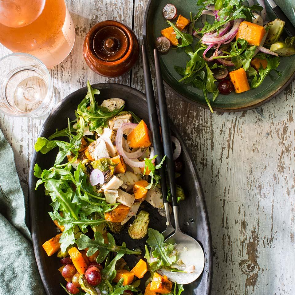 Hot roasted vegetables lightly wilt the arugula in this healthy dinner salad recipe. Keep prep time minimal with leftover chicken, precut butternut squash and trimmed Brussels sprouts.