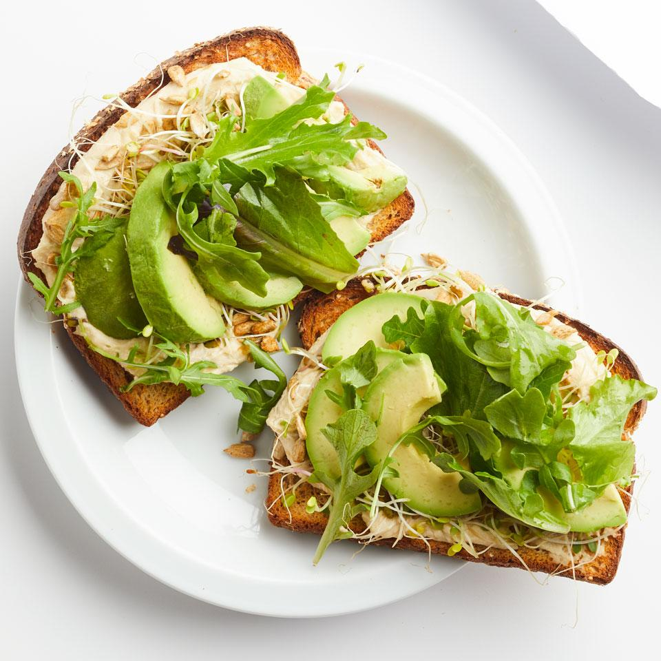 Hummus, sprouts and avocado top sprouted whole-wheat bread in this healthy vegan lunch idea. Look for sprouted bread in the freezer section of your grocery store.