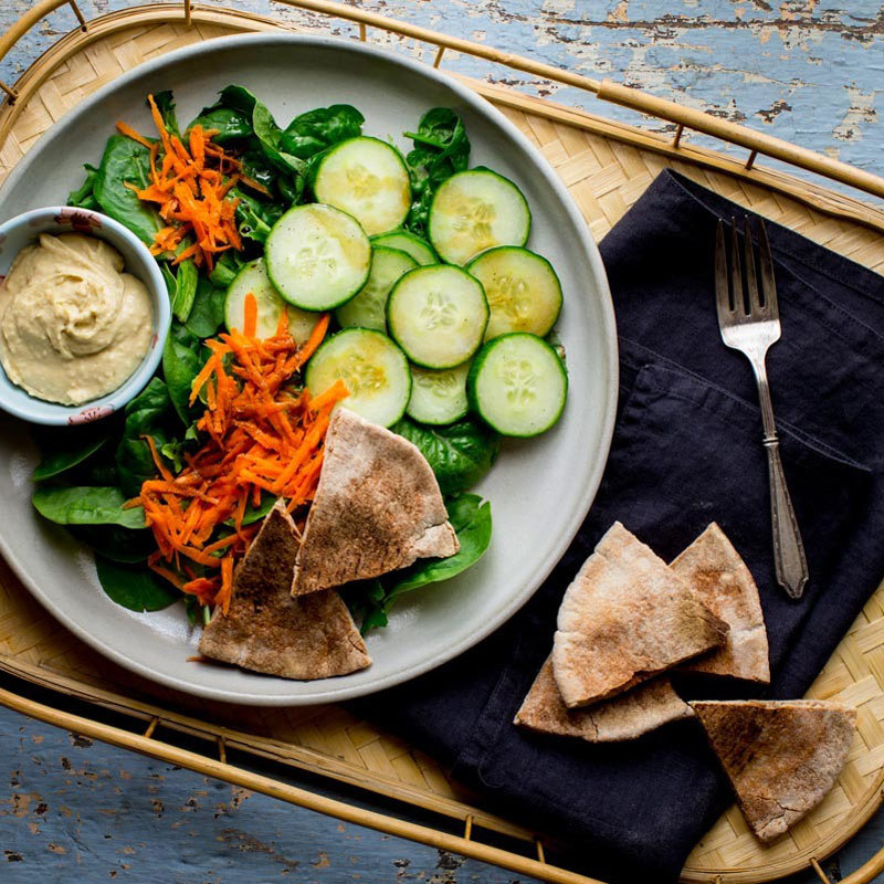 Elevate hummus and pita by piling your plate high with cucumbers, carrots and mixed greens! Just a drizzle of balsamic vinegar and extra-virgin olive oil is all it takes to dress it up.