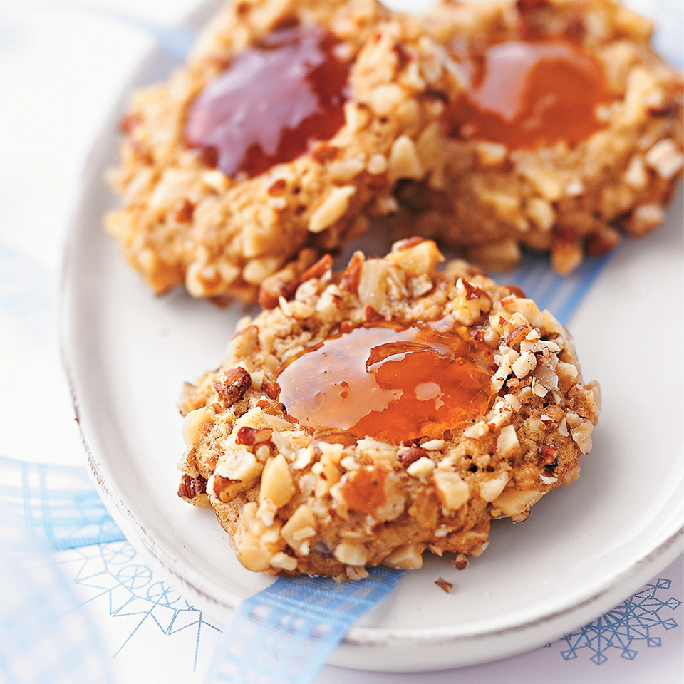 Little oatmeal cookies are rolled in nuts, baked, then filled with jewel-colored fruit preserves for a sweet and pretty treat.