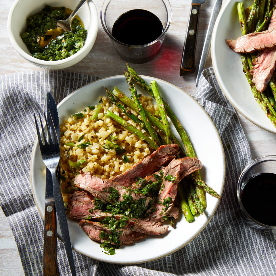 This elegant steak dinner for two features asparagus drizzled with a bright chimichurri sauce. A bed of cauliflower rice sops all the extra juices, but you could stir the herby sauce into the rice for extra flavor. This dish is easy enough for a weeknight dinner but delicious enough for date night or a dinner party.