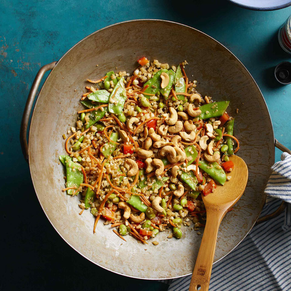 Substituting riced cauliflower for rice trims calories and carbs in this veggie-packed dish. Use the vibrant flavors of traditional fried rice—ginger, scallions and tamari—to create a low-carb fried rice version of the classic take-out meal.