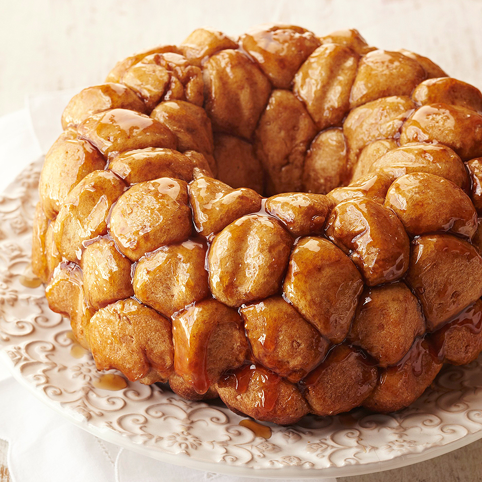 Monkey bread is a sweet bread made up of many small pieces of dough that are baked together into a single, large pastry. Each piece of monkey bread in this recipe contains a cherry and toasted walnut center, and a maple-brown sugar syrup coating.