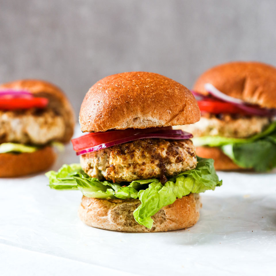 Burgers made with ground turkey are a lean alternative to beef burgers, providing you choose turkey ground from the breast. Regular ground turkey, which is a mixture of light and dark meat and some skin, contains almost as much fat as lean ground beef. A honey-mustard mixture keeps these low-fat patties moist and succulent.