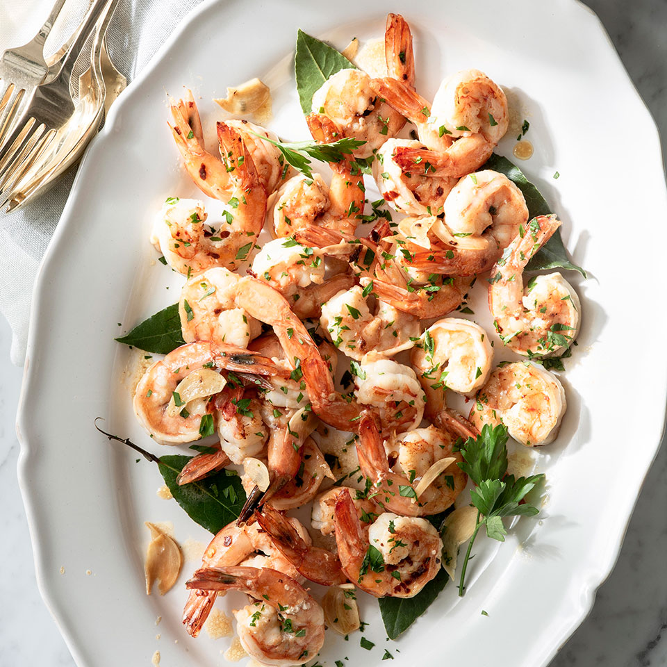 Peeled shrimp may be convenient, but here the shells—and heads if you are lucky enough to find them still on—are transformed into a quick stock that adds a boost of flavor. Serve the garlic-sautéed shrimp as an appetizer or use them as a topping for pasta or risotto.