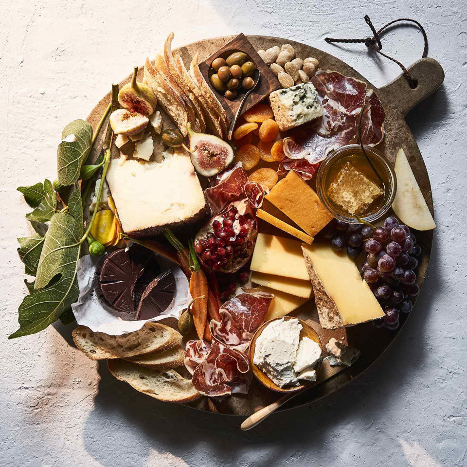 A cheeseboard is an ideal stationary hors d'oeuvre for holiday entertaining. Select a variety of cheeses, making sure to include an aged variety, a creamy cheese, a blue cheese and perhaps a smoked cheese. Round out the platter with cold cuts, bread, an abundance of seasonal fruits, dried fruit, crudité, nuts and olives. We even included some dark chocolate to cap it off!