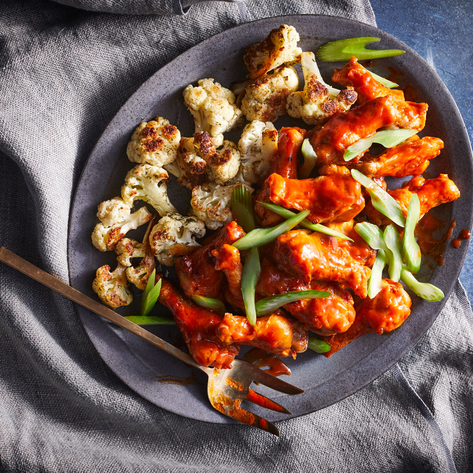 Our wings are broiled rather than deep-fried, which reduces greasiness and calories. Served with a side of sauced-up cauliflower to help tone down the spiciness and sneaking a few extra vegetables into game day makes this sheet-pan dinner just as healthy as it is delicious.
