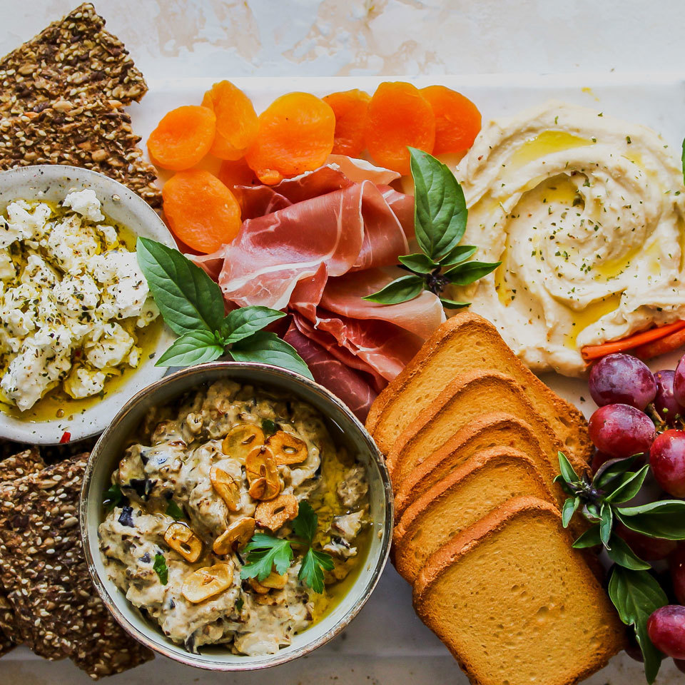 Channel the flavors of the Mediterranean in this bountiful appetizer board. A duo of classic hummus and roasted eggplant dip offers dunking options for seeded crackers, carrot sticks and raw fennel slices. Juicy grapes and dried apricots provide a sweet counterpart to salty prosciutto and feta cheese.