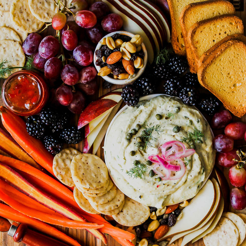 A dairy-free dip sets the tone for this vegan snack board. Rainbow carrots and crisp pear slices offer refreshing crunch and visual appeal, while an assortment of seeded crackers and mini toasts make blank canvases for spreads and jams. Blackberries and grapes lend a fresh and fruity finish.