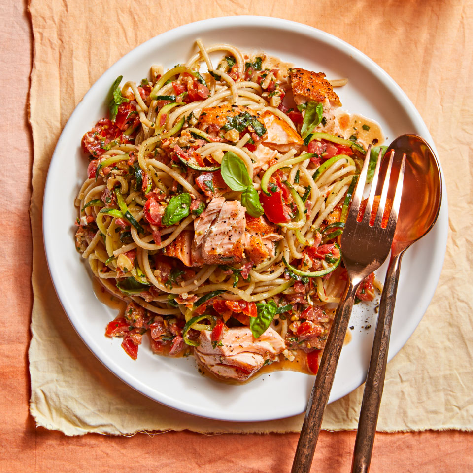 Trapanese pesto is the Sicilian version of the sauce that uses tomatoes and almonds instead of pine nuts. This savory pesto sauce coats low-carb zucchini noodles and heart-healthy seared salmon to create an absolutely delicious pasta dinner.