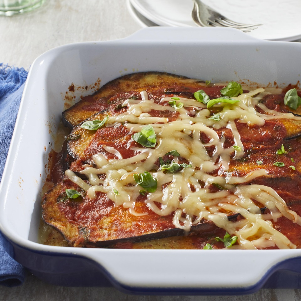 For this healthy take on baked eggplant Parmesan, we've swapped out the traditional mozzarella and Parmesan cheese for Cheddar. A simple tomato sauce and a sprinkle of fresh basil brighten up the flavors in this easy dinner that'll please the whole family. Try it the next time you have a bumper crop of eggplant!