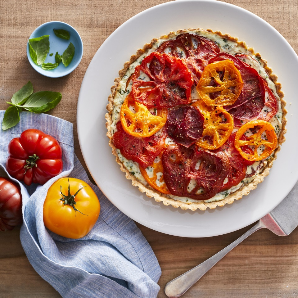 Unlike the classic Southern version of tomato pie, which relies on mayonnaise and Cheddar cheese, this colorful pie gets its creamy texture and savory flavor from herb-speckled ricotta and Parmigiano-Reggiano cheese. A simple stir-together olive oil dough is patted into the tart pan—no rolling pin required. Look for heirloom tomatoes in a variety of colors and sizes for the prettiest and tastiest pie. Serve this tart with a simple green salad for brunch, lunch or light dinner.