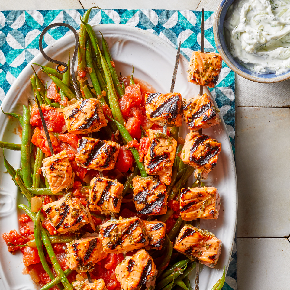 This easy grilled salmon recipe is sure to help you win your next backyard BBQ. Lemon, garlic and herbs make a simple, flavorful marinade for the healthy fish souvlaki (souvlakia is the Greek word for kebabs), and the yogurt-based tzatziki sauce is one of the traditional pleasures of Mediterranean cuisine. A side of Greek-style green beans completes this healthy dinner recipe that's as suited to entertaining as it is to family meals.
