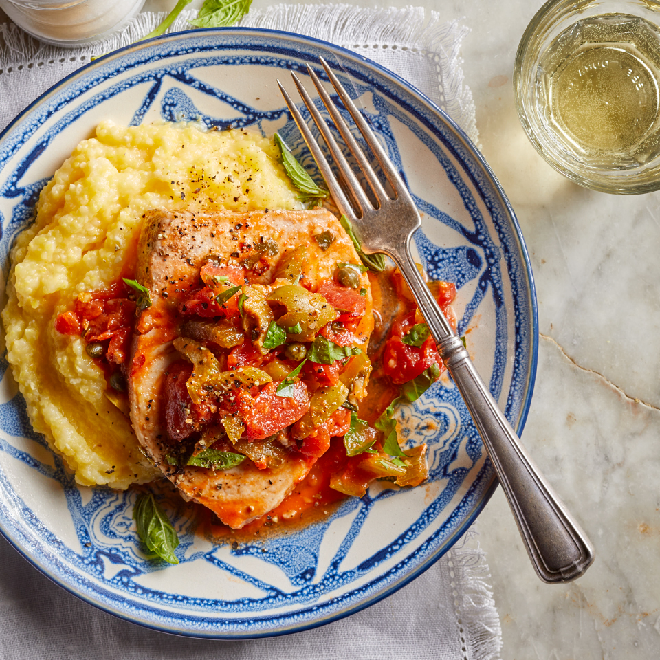Dive deliciously into the Mediterranean diet with this healthy fish recipe, which takes its inspiration from southern Italy. In Sicily and Calabria, the ghiotta style of cooking involves simmering fish or meat with celery, olives, capers, basil and tomatoes. Serve the fish and sauce over creamy polenta for an easy dinner recipe that requires just 20 minutes of active prep time.