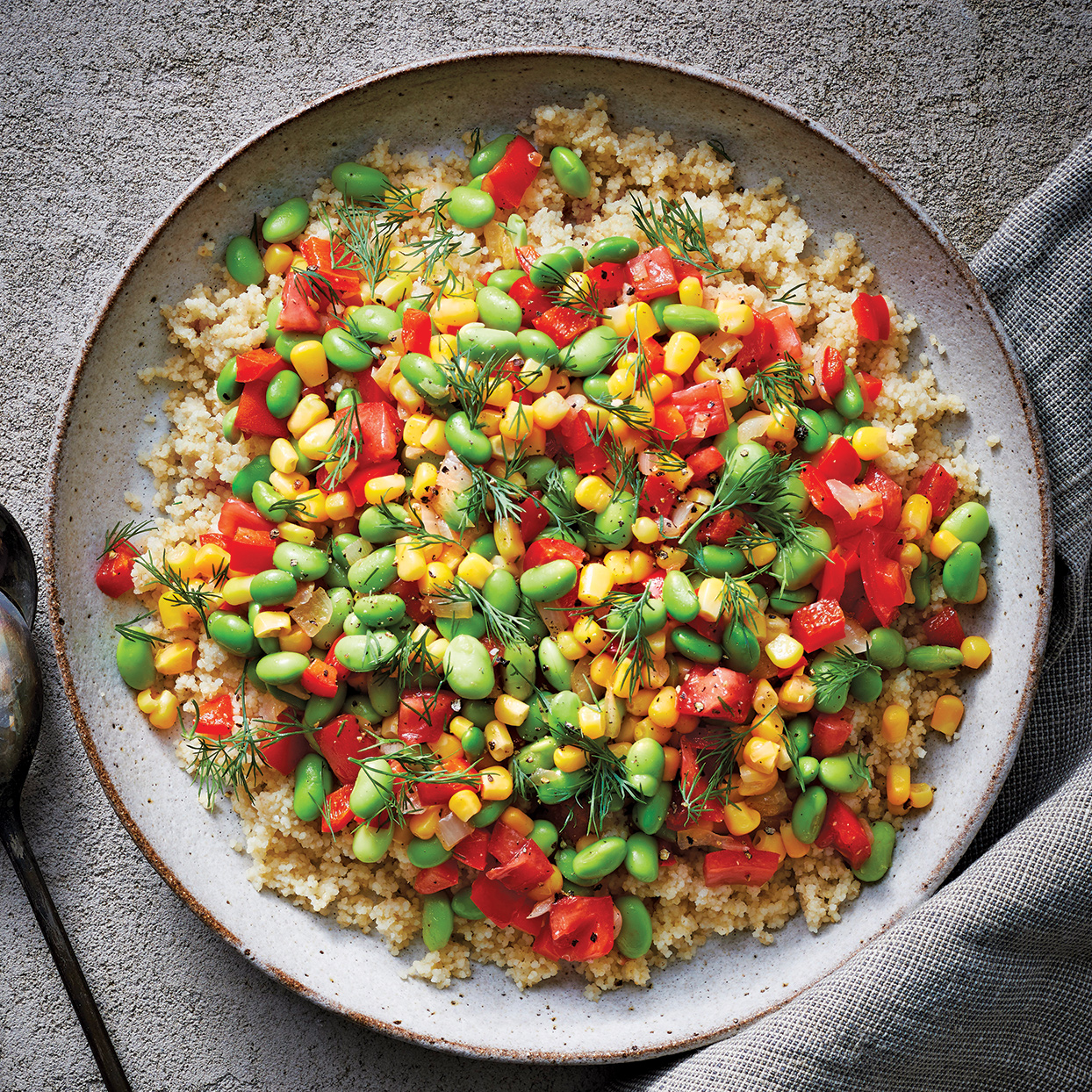 Vegetables and edamame (soybeans) crown a bed of whole-wheat couscous for a hearty, healthy meal. You can use fresh-shelled edamame and fresh corn, but using the frozen varieties saves time and produces the same delicious results.